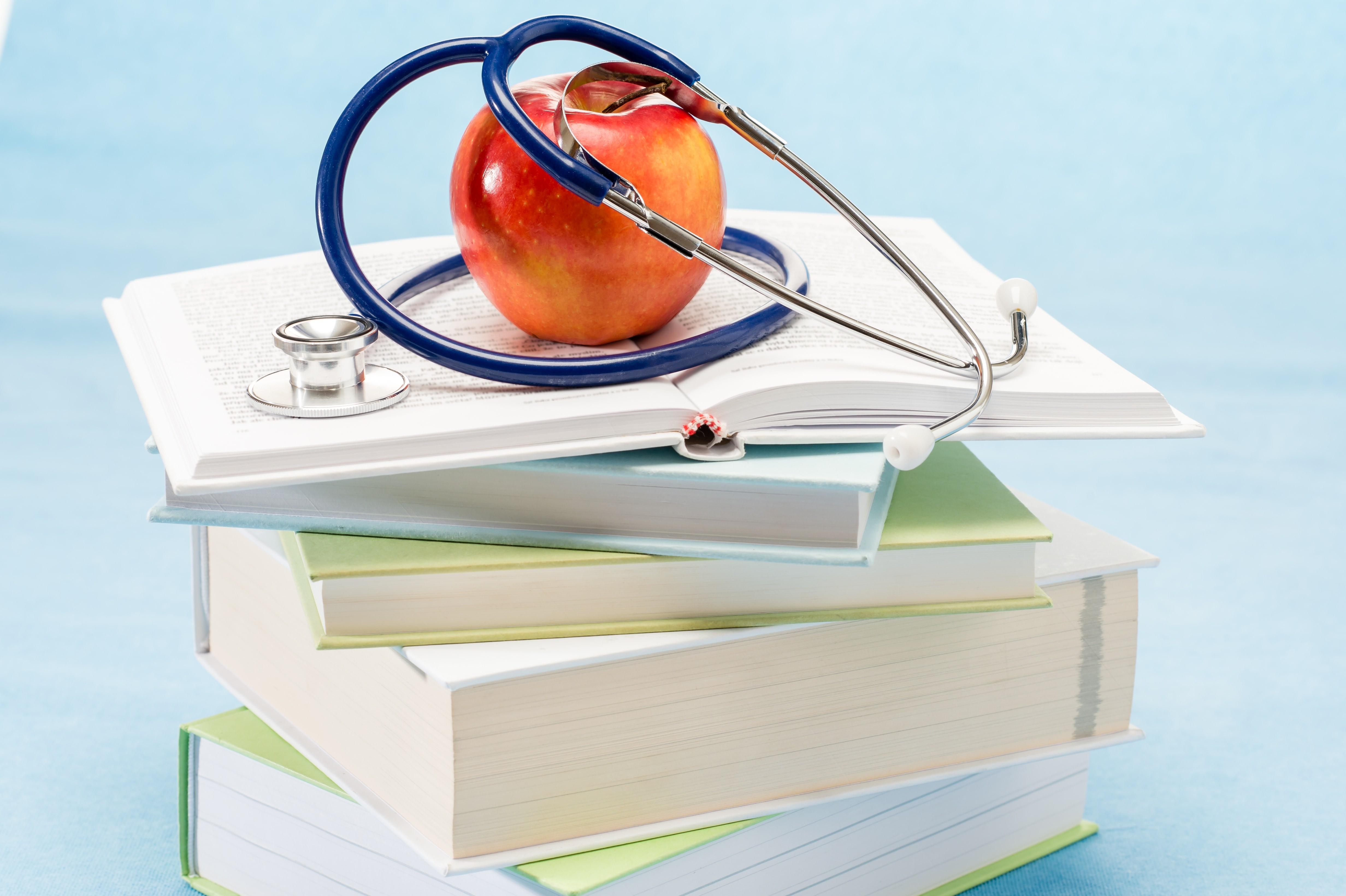 Medical Books stacked with Apple on Top